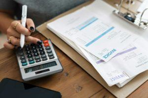 woman with black nails holding white pen above calculator with invoice papers on desk beside it