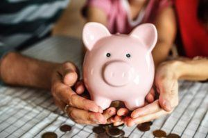 hand of man woman and child holding pink piggy bank with coins in front of it