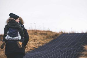 person wearing winter jacket with young child strapped to their back while walking along pathway