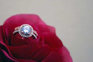close up shot of diamond ring sitting within the petals of a red flower
