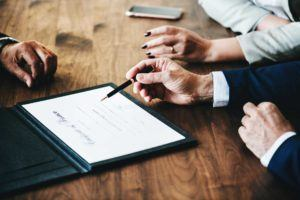 hands of three people at wooden desk with one person holding pen and pointing towards document