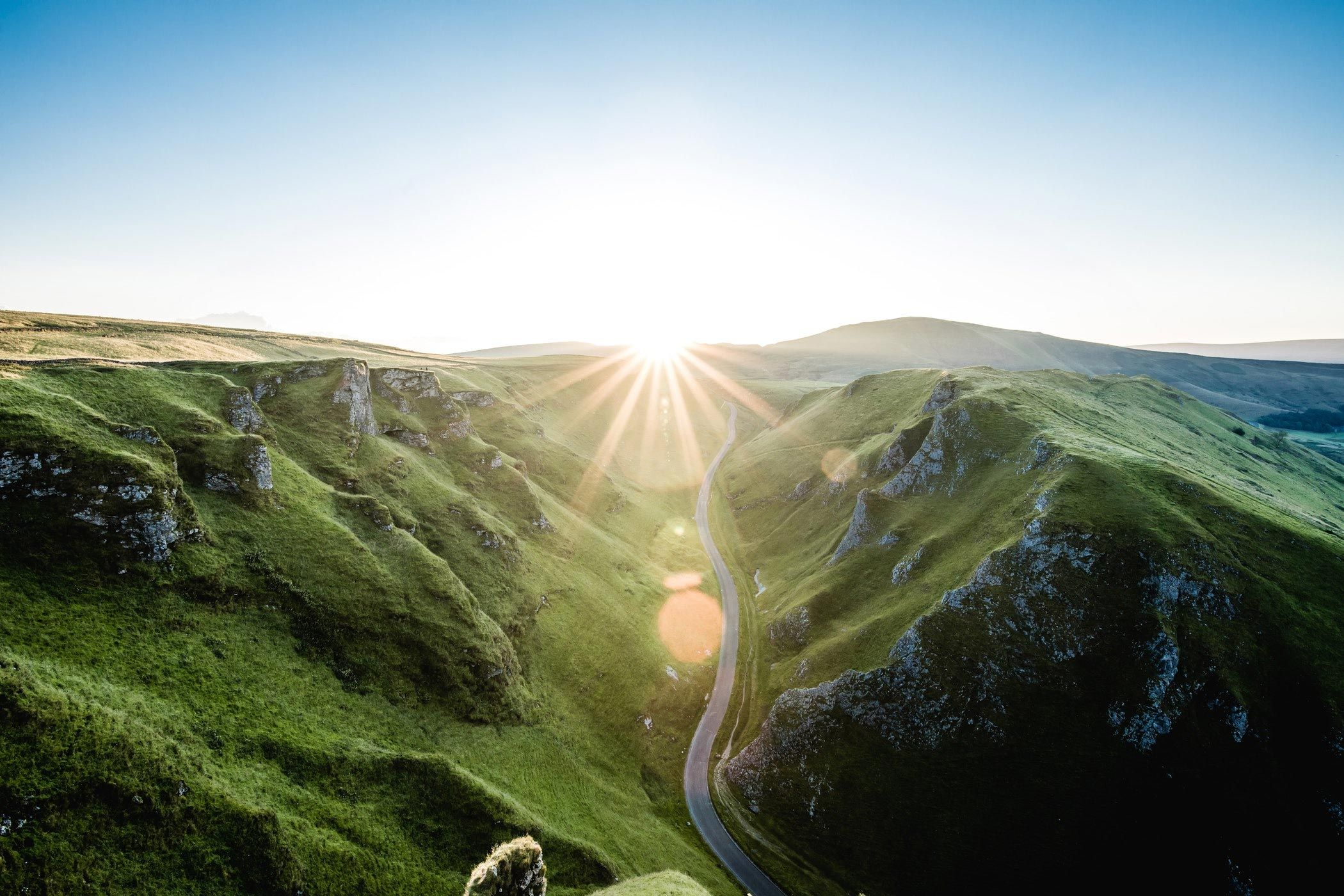 aerial landscape shot with road in the middle of large green hills leading towards sun rising over horizon