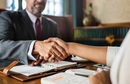 man in suit shaking hands with person at table with documents
